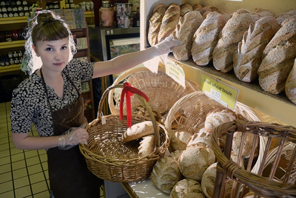 Marie, an employee at Uppercrust Bakery in Gainesville, stocks fresh bread on the shelves.