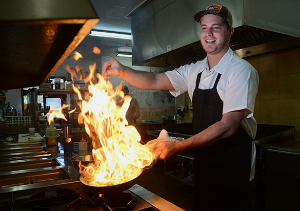 Mike Riska, a chef at the Jones B-Side in downtown Gainesville, makes some fire for the camera.
