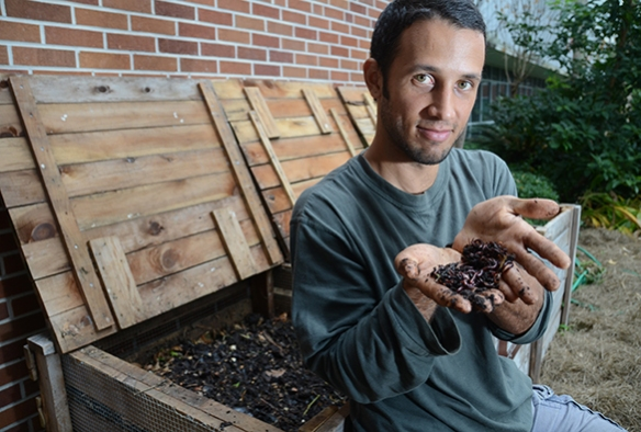 Chris Cano, of Gainesville Compost, poses with worms near some of his compost bins.