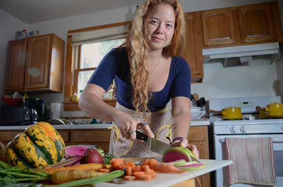 A woman chops vegetables, including a watermelon radish, at home.