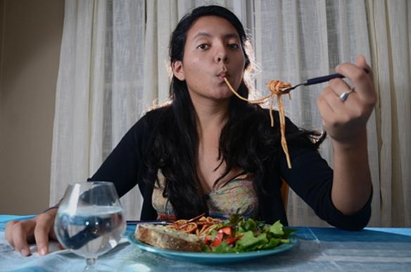 A woman eats spaghetti.