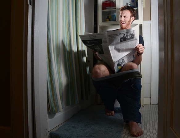 A man reads the newspaper while pooping.