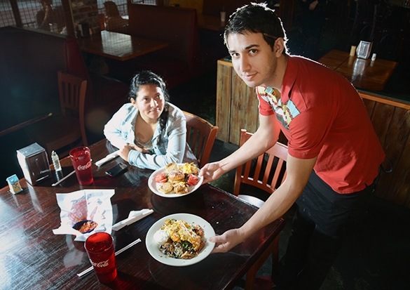 A server at Boca Fiesta in downtown Gainesville brings out his customers' dishes.
